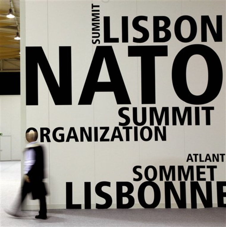 A man walks by a logo printed on a wall inside the NATO summit venue in Lisbon, Portugal on Thursday. Heads of State of NATO member countries gather for a two day summit beginning on Friday, and will discuss such topics as Afghanistan and missile defense.