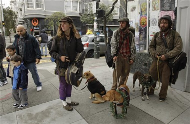 From right, Joe Lust, 20, of Austin, Tex., Steven Grossman, 21, of Fort Collins, Colo., and Liz Mallion, 22, of Hawaii stand with their dogs on April 20 at the corner of Haight and Ashbury streets in San Francisco. A year after a controversial prohibition against sitting or lying on sidewalks was proposed, police have begun enforcing the law along the city's most famous stretches of streets. But renewed squabbling has broken out between those who say the law is working and those who say it is unenforceable and unfairly targets the homeless.