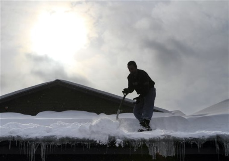 The sun begins to break through the clouds as Anesti Karathanasis works to shovel snow from the latest storm off the roof of his restaurant on Friday in Concord, N.H.