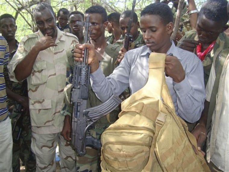 Somali government forces show off the gun and hand luggage that were retrieved from the body of Fazul Abdullah Mohammed, June 8.