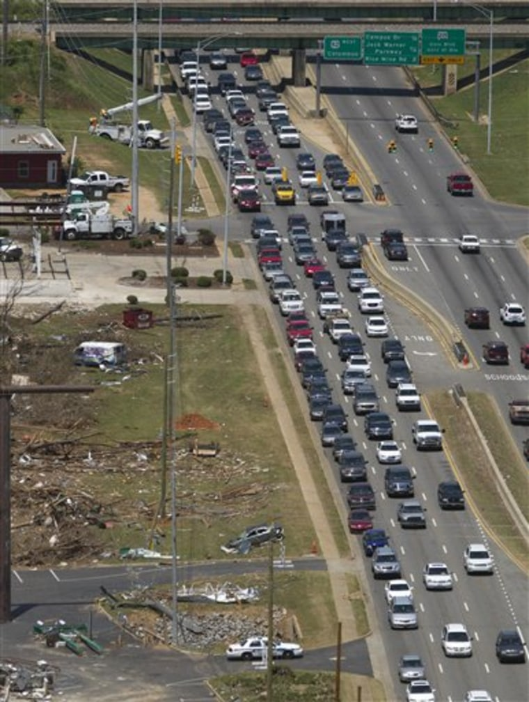 Heavy traffic rolls slowly down McFarland Blvd. past tornado damage in Tuscaloosa, Ala., Saturday, as volunteers flooded into the tornado ravaged parts of Alabama in such great numbers that the governor's office warned people to be patient with traffic jams.