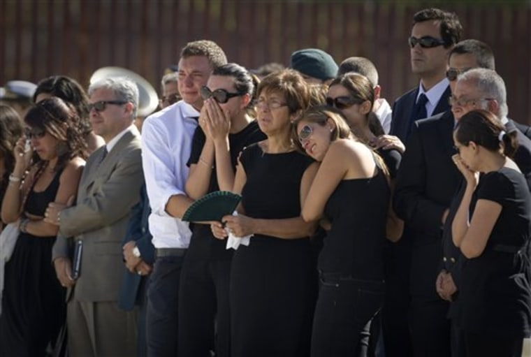 Relatives react as the coffins of three Spaniards killed in Afghanistan are brought back to Spain.
