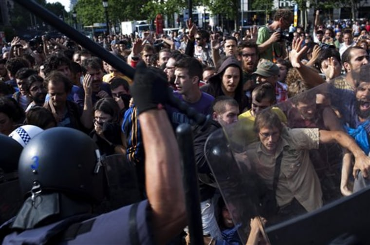 Riot police disperse demonstrators during clashes in Barcelona, Spain, on Friday.