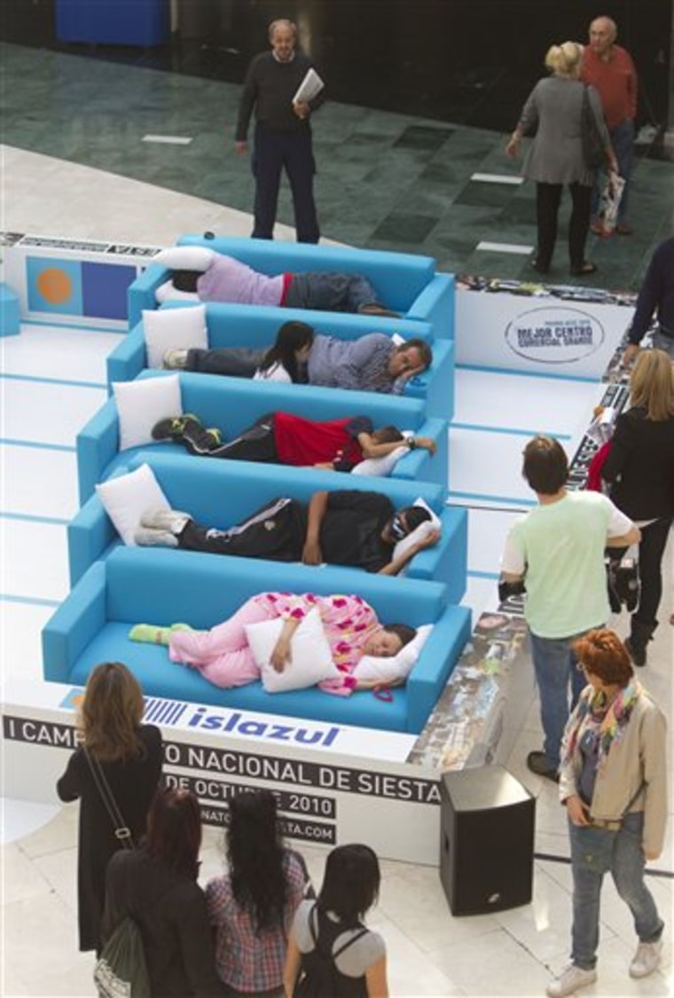 People sleep a siesta on couches Wednesday during the first siesta championship in Madrid.
