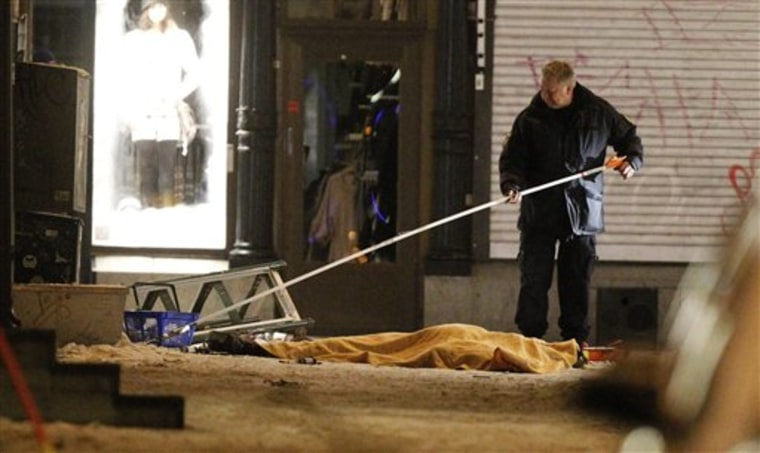 Police forensics expert at the scene of an explosion in Stockholm on Saturday. Two explosions in central Stockholm killed one person and injured two, causing panic among Christmas shoppers. Police spokeswoman Petra Sjolander said a car exploded near Drottninggatan, a busy shopping street in the center of the city.