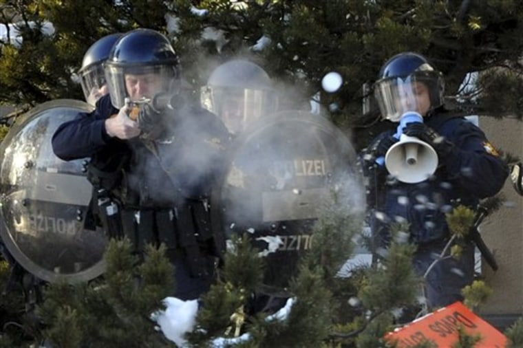 Police fire rubber bullets at protestors outside the meeting hall of the World Economic Forum in Davos, Switzerland, on Saturday. More than two dozen senior officials from key economies will try to agree on whether to send a political signal that a new global trade deal can, at last, be completed this year.