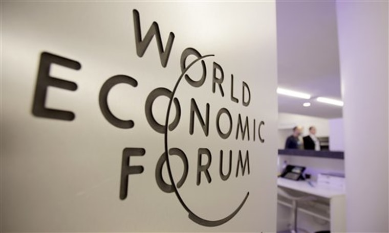People walk by a sign in the meeting center at the World Economic Forum in Davos, Switzerland.