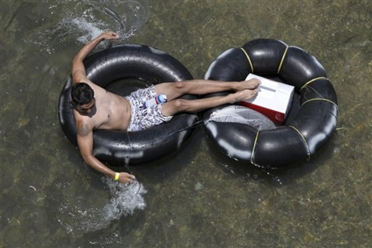 In a May 28, 2012 photo, a tuber floats down the Comal river Memorial Day in New Braunfels, Texas. Drinking beer while lazily floating through New Braunfels is a heat-beating tradition for hundreds of thousands of vacationers each summer, but turnout is down and businesses say the reason is clear: a new ban on disposable containers.