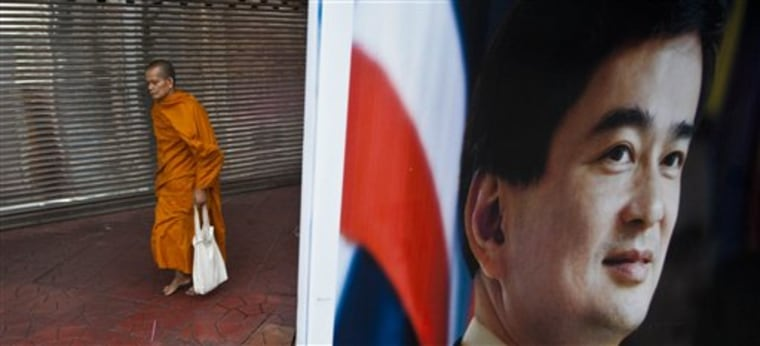 A Buddhist monk walks near an election poster for Prime Minister Abhisit Vejjajiva of Thailand's Democrat party during morning rounds in Bangkok on Sunday.