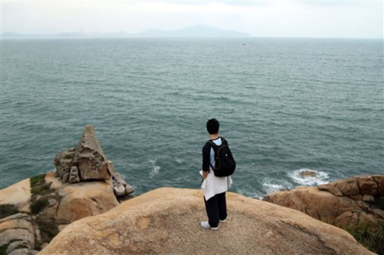 A visitor looks out at the sprawling green waters of the South China Sea as seen from red, granite cliffs in Cheung Chau, Hong Kong. Just eight miles from Hong Kong's Central Pier, Cheung Chau was once a pirate's cove — a place where renegades of the South China Sea stashed their booty. Today, it is a hideout for tourists and locals alike, and makes for a perfect escape from the big city.