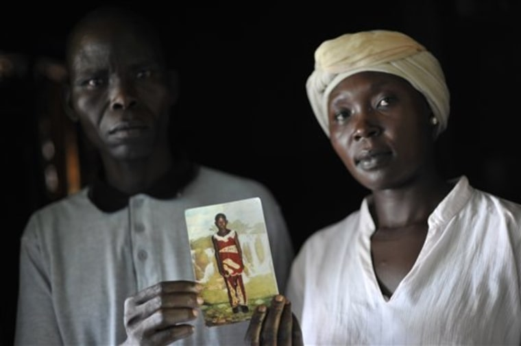 Balluonzima Christ and Rose Ajiba hold a photograph of their child Caroline Aya, who was killed and had her tongue cut out — a sign that she was probably a human sacrifice in a ritual killing in Jinja, Uganda.