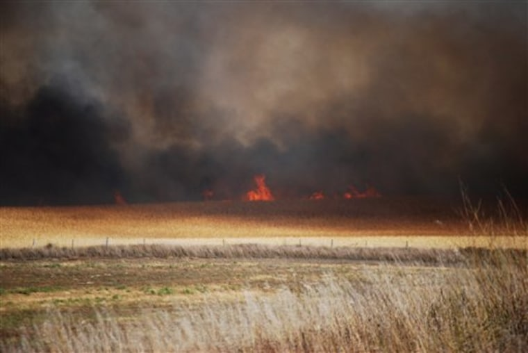 Flames and clouds of smoke billow over fields in southern Logan County, Neb., on Tuesday.