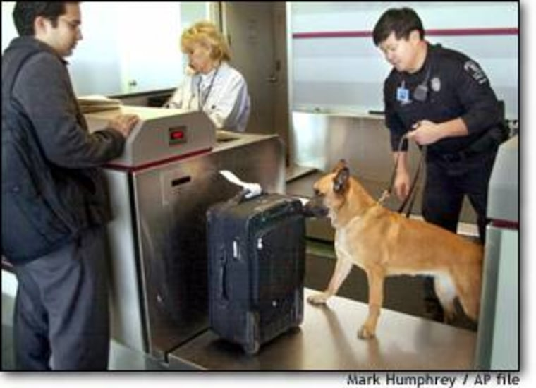 K-9 officer Vince Dy and his search dog, Rexie, check a passenger's bag at the Nashville, Tenn., airport.
