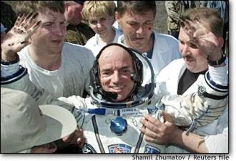 The world's first paying space passenger, Dennis Tito, gestures after landing in Kazakhstan on May 6, 2001.