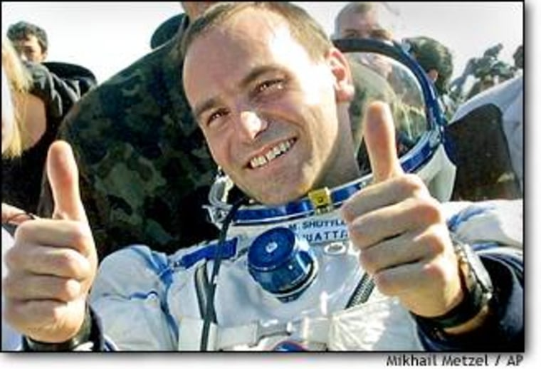 South African Internet millionaire Mark Shuttleworth, the world's second paying space passenger, gives a thumbs up on Sunday after landing near the Kazakh town of Arkalyk.