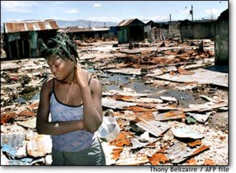 A Haitian woman wanders among the wreckage in the Cite Soleil slum of Port-au-Prince in April after hundred of houses were destroyed and 10 people killed during rioting between local residents.