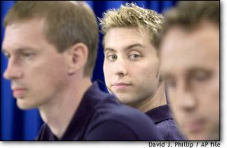 'NSync singer Lance Bass, center, listens with fellow crew members during a news conference at Johnson Space Center in August.
