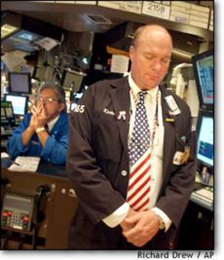 Trader Kevin Lodewick, right, observes a moment of silence on the floor of the New York Stock Exchange Wednesday at 9:59 a.m., the time the first of the World Trade Center buildings collapsed one year ago.