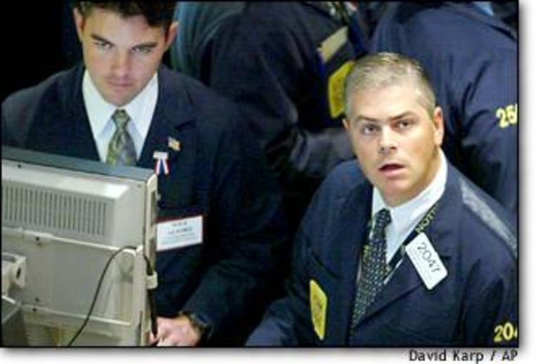 Specialists and treaders working on the floor of the NYSE watch the monitors Tuesday as the Dow surges 378 points.