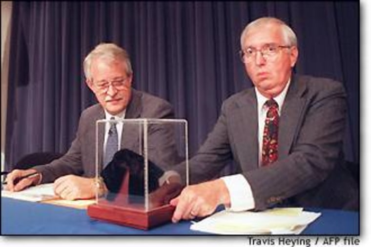 NASA planetary scientist David McKay, at right, unveils the Martian meteorite ALH84001 as NASA Associate Administrator Wesley Huntress looks on during an August 1996 news conference.
