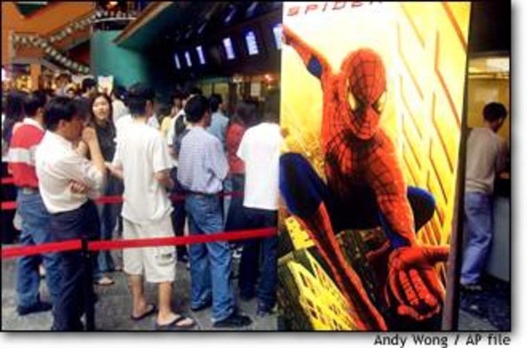 """Malaysians wait in a line to see """"Spider Man"""" at a cinema in Kuala Lumpur on April 30. Many interviewees gave the United States high marks on its films."""