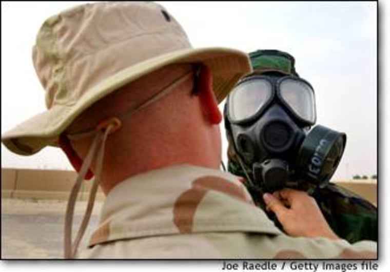 U.S. Marine Cpl. Dusty Mathews puts on a chemical protection suit and gas mask with help from Sgt. Darrin Minderman at Camp Commando in Kuwait on Dec. 3.