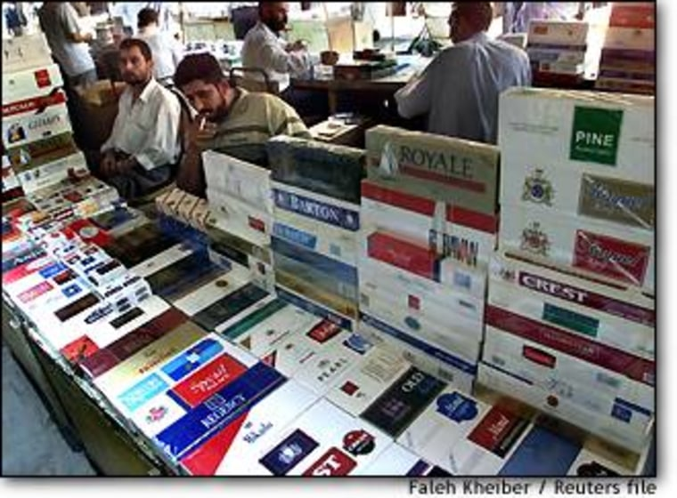 Iraqis sell cigarettes in a Baghdad market in October. Cigarette maker R.J. Reynolds Tobacco has illegally funneled millions of dollars worth of cigarettes into Iraq in violation of trade sanctions, according to a lawsuit filed recently by the European Union.