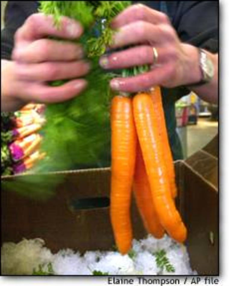 Dan Johnson, produce coordinator at the Puget Consumers Co-op in Seattle's Greenlake neighborhood, bundles organic carrots.