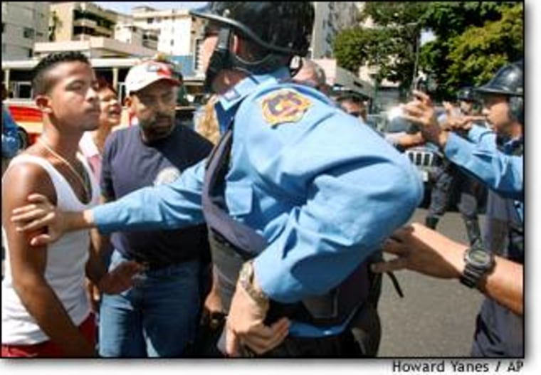 Police officers scuffle with opposition demonstrators blocking a street in Caracas on Wednesday.