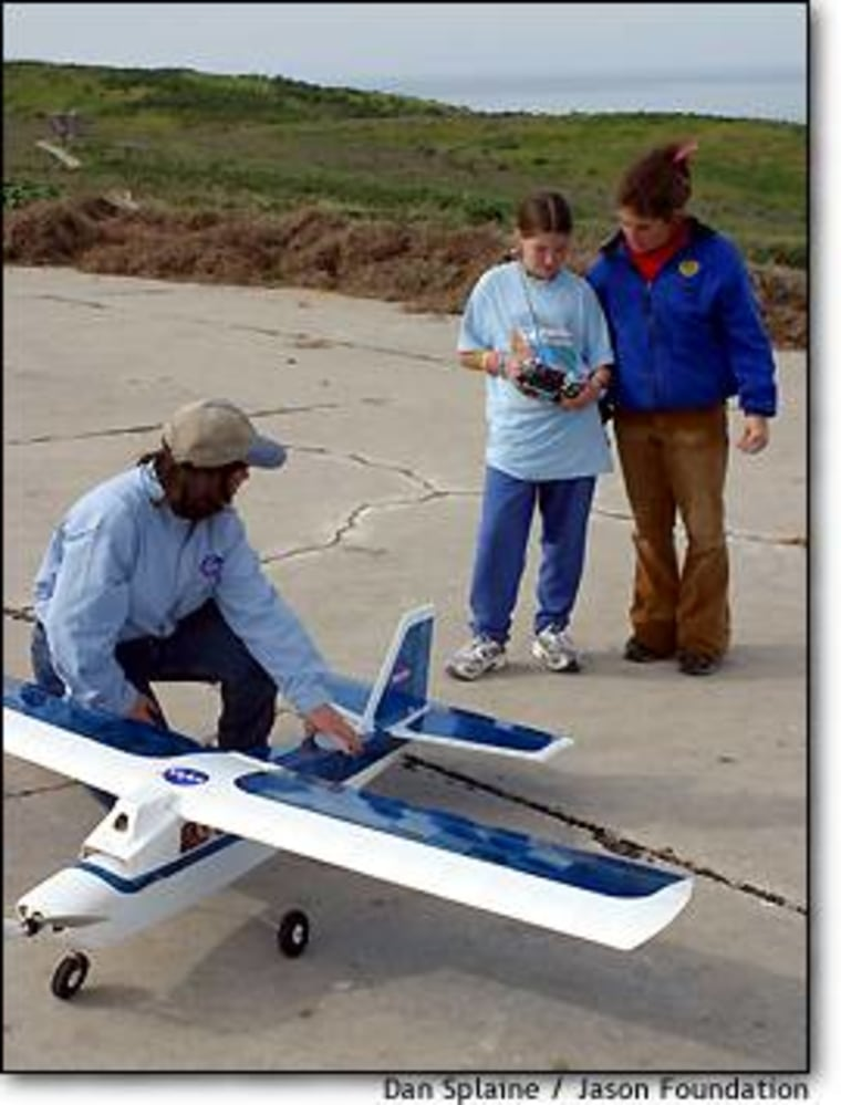 NASA education specialist Sallie Smith steadies one of NASA's experimental camera-equipped planes as student-researchers Rachel Sheppard and Gina Pambianchi go through a checklist.