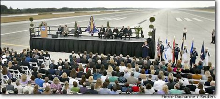 NASA workers attend a memorial service for the Columbia astronauts on a runway at the Kennedy Space Center in Cape Canaveral, Fla.