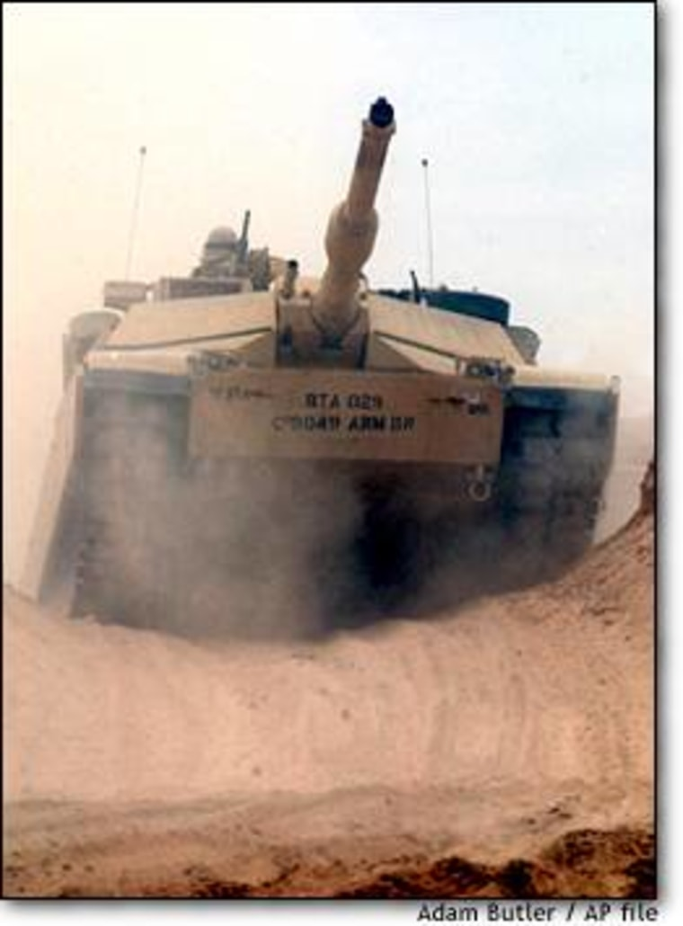 An Abrams tank climbes over a dune duinng a military exercise in the western Kuwait desert in December.