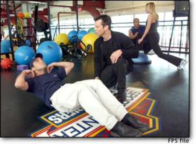 Bob Greene, right, a personal trainer and author, helps a client at the Sports Center at Chelsea Piers in New York on March 11.