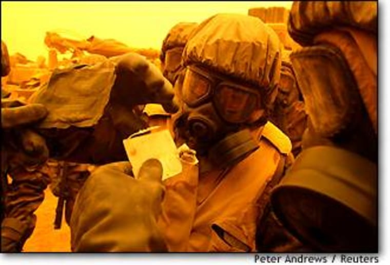U.S. soldiers in chemical protection suits conduct a chemical detection test during a false alarm alert in a sandstorm in southern Iraq on March 26.