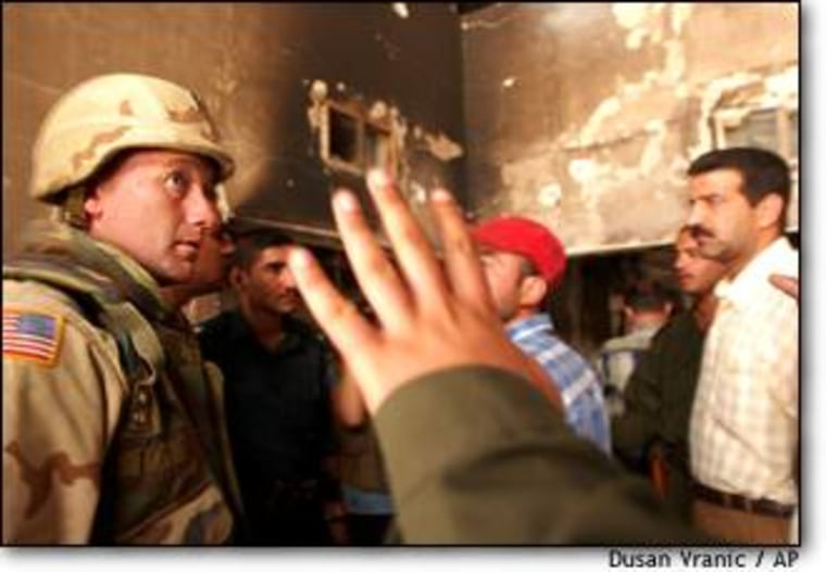A U.S. Army soldier listens to an Iraqi police officer inside a burned and looted bank in central Baghdad on April 21.
