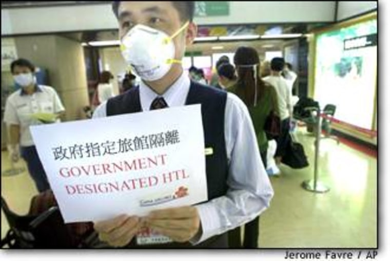 """A China Airlines employee, holding a sign that reads """"Government Designated Hotel,"""" directs quarantined passengers arriving from Hong Kong at Taiwan's Chiang Kai-shek International Airport on April 28."""