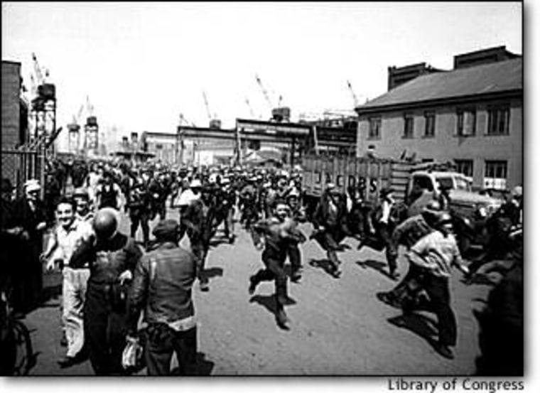 Workmen at Baltimore's Bethlehem-Fairfield shipyards run to punch the clock at the end of their shift in May 1943.