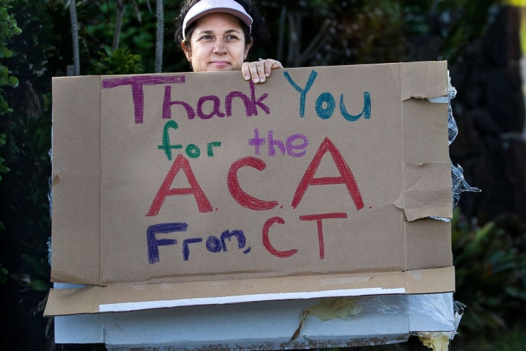 A woman holding a sign in support of the Affordable Care Act is seen as President Barack Obama's motorcade returns to his vacation compound from the gym at Marine Corps Base Hawaii on December 29, 2013 in Kaneohe Bay, Hawaii.
