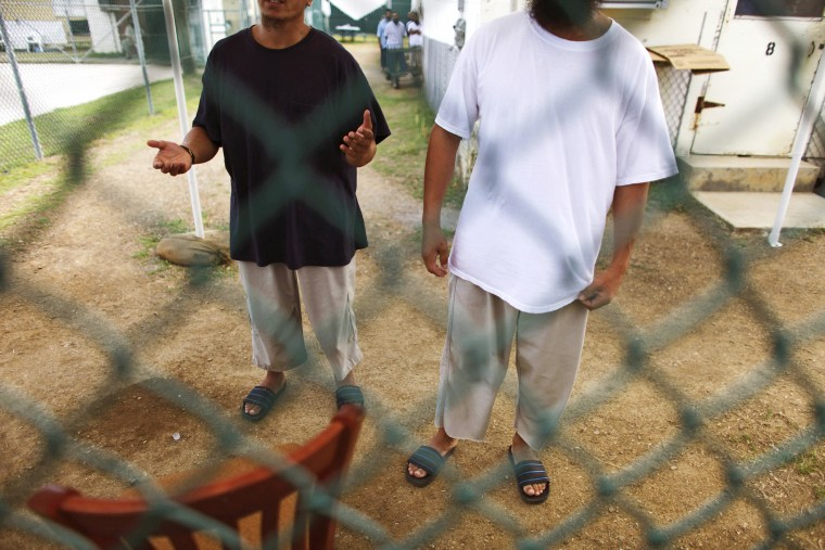 Chinese Uighur Guantanamo detainees try to talk to visiting members of the media at Camp Iguana detention facility in Guantanamo Bay, June 1, 2009.