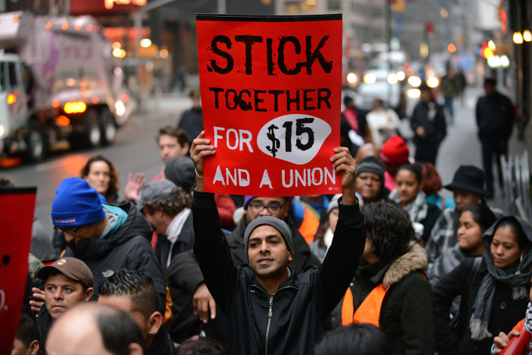 A protester holds up a placard as fast food workers and union members demonstrate in New York City, December 5, 2013.
