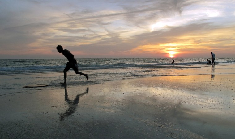 A beachgoer jumps on his 'boogie board' at sunset on a beach in Bradenton, Florida, May 18, 2010.