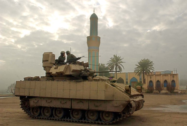 U.S Army soldiers of the 1st Battalion, 22nd Regiment, (1-22) of the 4th Infantry Division, talk onboard their M1 tank in front of a mosque in Tikrit, Iraq. (AP Photo/Gregorio Borgia)