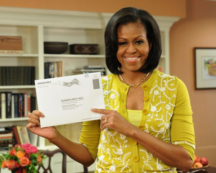 First Lady Michelle Obama poses with her absentee ballot on Oct. 15th, (Photo: Obama for America/Jocelyn Augustino)
