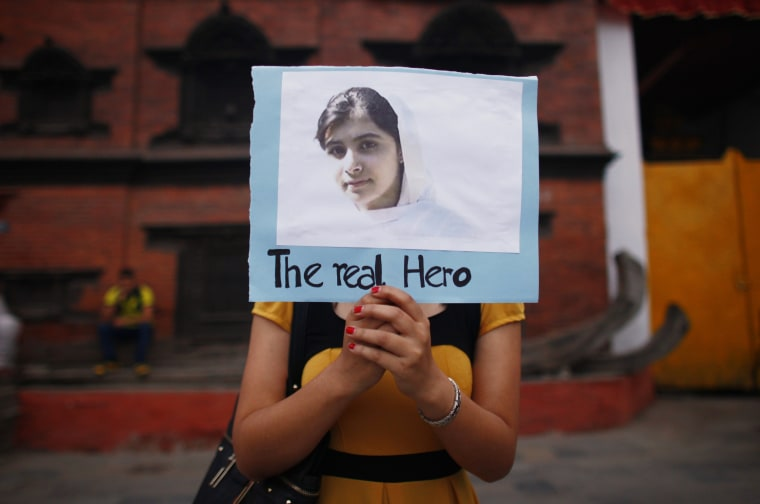 A Nepalese student holds a photo of Pakistani schoolgirl Malala Yousafzai, during a candlelight vigil to express support for her. (AP Photo/Niranjan Shrestha)