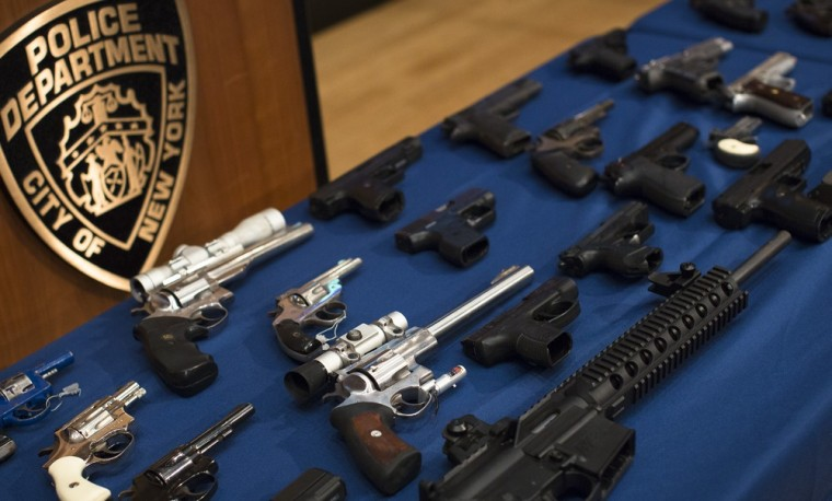 Nearly 100 confiscated illegal firearms rest on a table before a press conference with Mayor Michael Bloomberg, NYPD Commissioner Ray Kelly, and NYC District Attorney Cyrus Vance, Friday, Oct. 12, 2012 in New York.