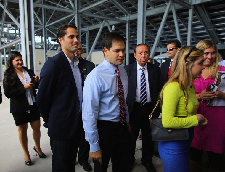Craig Romney the son of Mitt Romney (L) and Sen. Marco Rubio (R-FL) wait together to enter a building for a  Mitt Romney campaign rally at Florida International University in Miami, Florida. on October 12, 2012 in Miami, Florida.