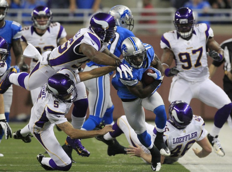Minnesota Vikings outside linebacker Marvin Mitchell (55) and punter Chris Kluwe (5) take down Detroit Lions' Stefan Logan (11) as he returns a punt during the third quarter of an NFL football game against the Minnesota Vikings at Ford Field in Detroit...