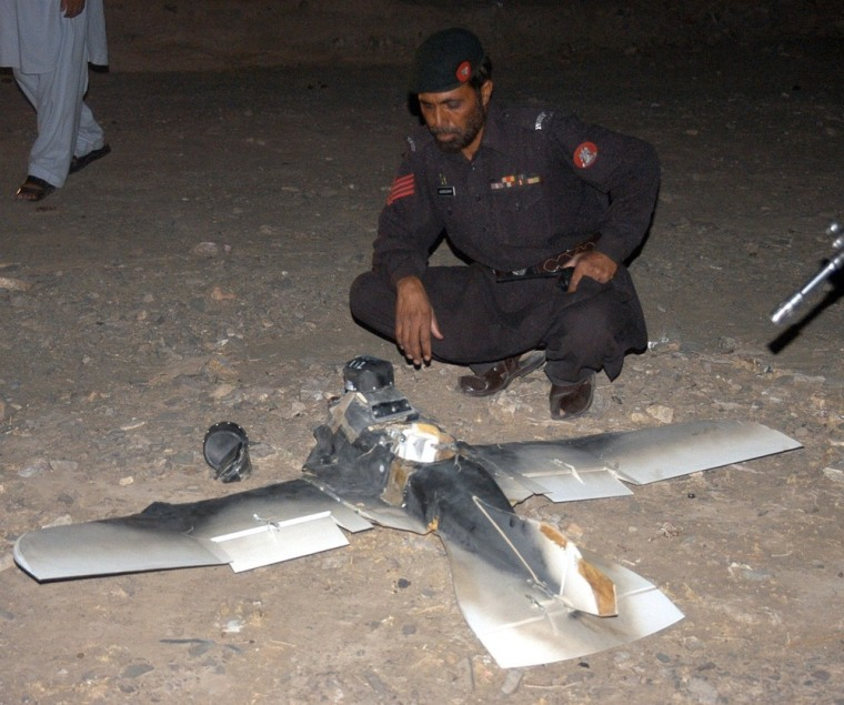 This file photo taken on August 25, 2011 shows Pakistani security personnel examining a crashed US surveillance drone some two kilometers inside Pakistani territory. (ASGHAR ACHAKZAI/AFP/Getty Images)