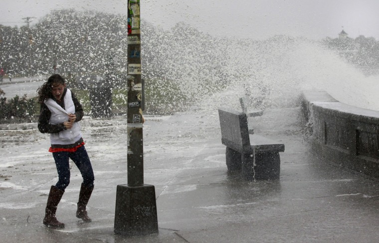A woman reacts to waves crashing over a seawall in Narragansett, R.I., Monday, Oct. 29, 2012. Hurricane Sandy continued on its path Monday, as the storm forced the shutdown of mass transit, schools and financial markets, sending coastal residents...