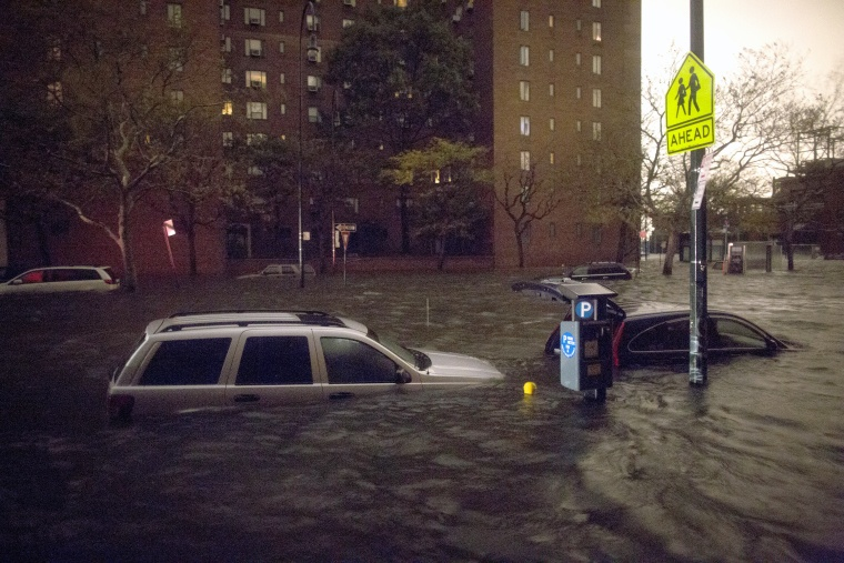 Vehicles are submerged on 14th Street near the Consolidated Edison power plant, Monday, Oct. 29, 2012, in New York. (AP Photo/ John Minchillo)